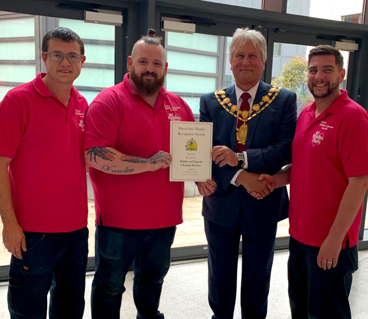 The Bubble & Squeak guys receiving the mayor's award for the charity word as back of the giving back page.